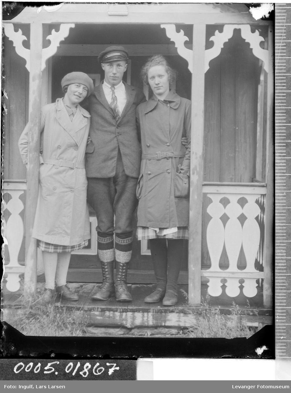 Portrett av tre ungdommer ved et inngangsparti.