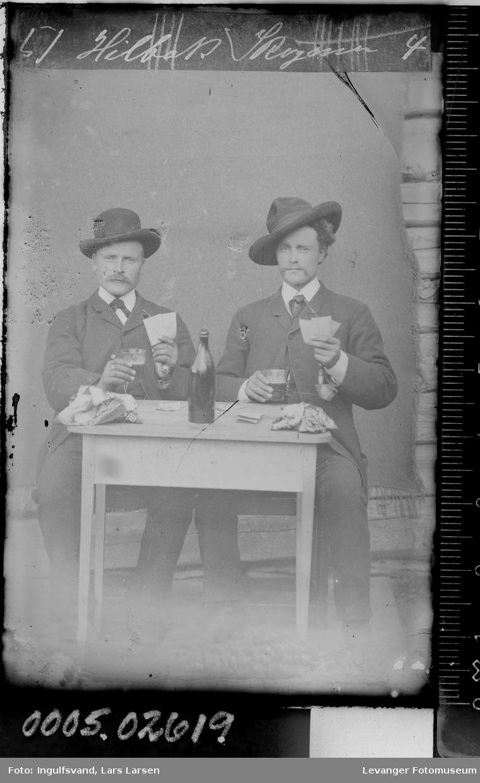 Portrett av to menn ved et bord som spiller kort.