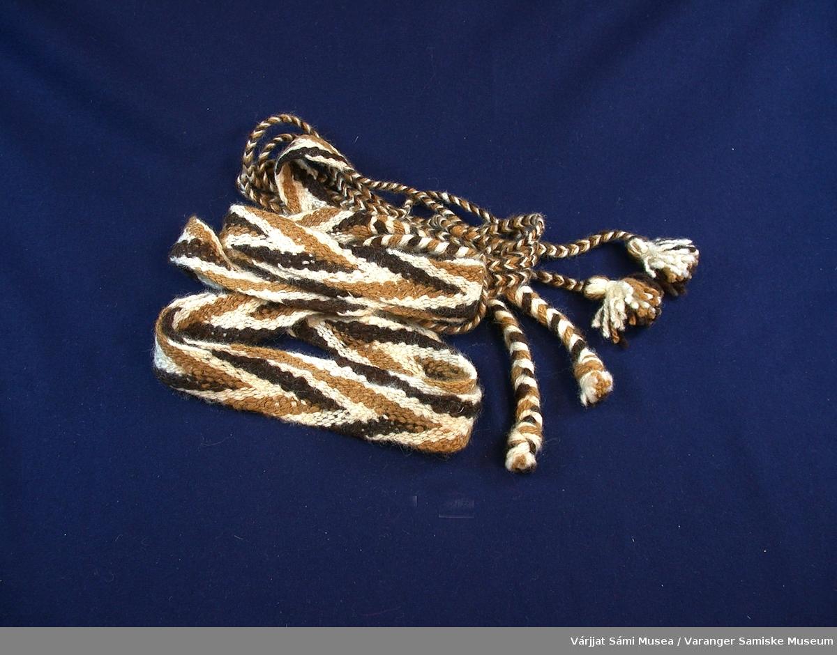 Innkjøpt fra VSMs duodjikonkurranse 2000  621-1: Pose av lakseskinn med front-dekor av rødt klede og perlebroderi. Perlebroderiet er geometrisk og i hvitt, blått og gult.  Høyde: 14 cm     Bredde: 8 cm      621-2: Flettede skallebånd av ull i mørkebrunt, lysebrunt og naturhvitt. Mønsteret ser ut som en flette. I endene er det tvunnede og flettede snorer i de samme fargene.   621-3: Strikkede votter av ull. Hovedfargen er naturhvit med mønster i mørkebrunt og lysebrunt.