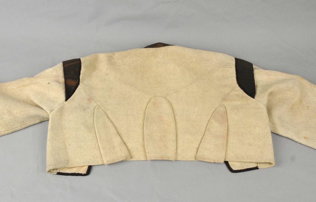 Trøye av gråkvit vadmål med ståkrage og med tosaums armar (desse er fasongklipt). Bryningar utfrå skuldrene. Kanta med svart ullklede nede rundt armane, langs framkantane, rundt nakken og på skuldrene. Utanfor denne i en smal tittekant (0,3 cm) i mørk vinraudt klede. Same kanting i skuldersaumen.  Ryggen ar samansett av to delar og med tre kilar (flasker) sett inn i saumane. Desse er holdt saman med ein i tvinna lintråd på vranga. Ei lomme i bomullstøy på innsida av venstre framstykke. Sydd for hand med lintråd. Med attersting og sårkantane er kasta over samla.