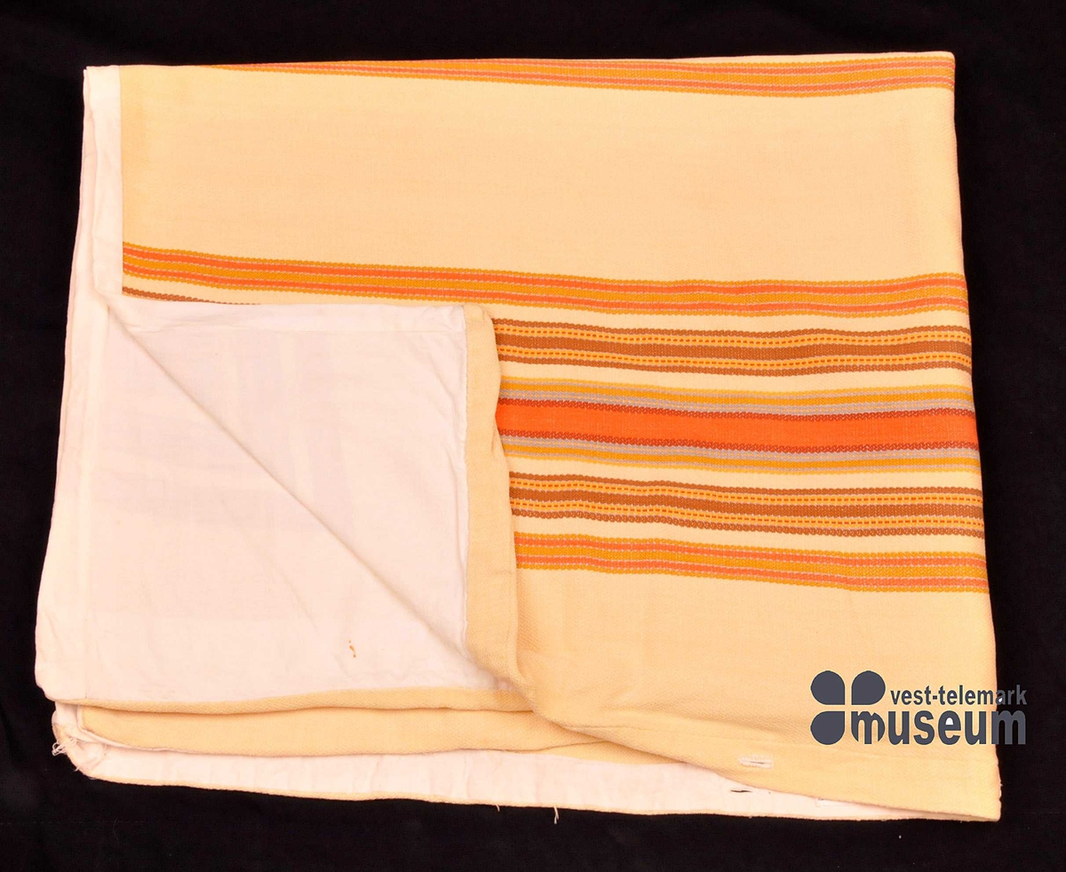 Dynetrekk der oversida er vove. Undersida er av einsfarga bomull. Vevnaden er i striper. Opning med knapphol i kortenden.