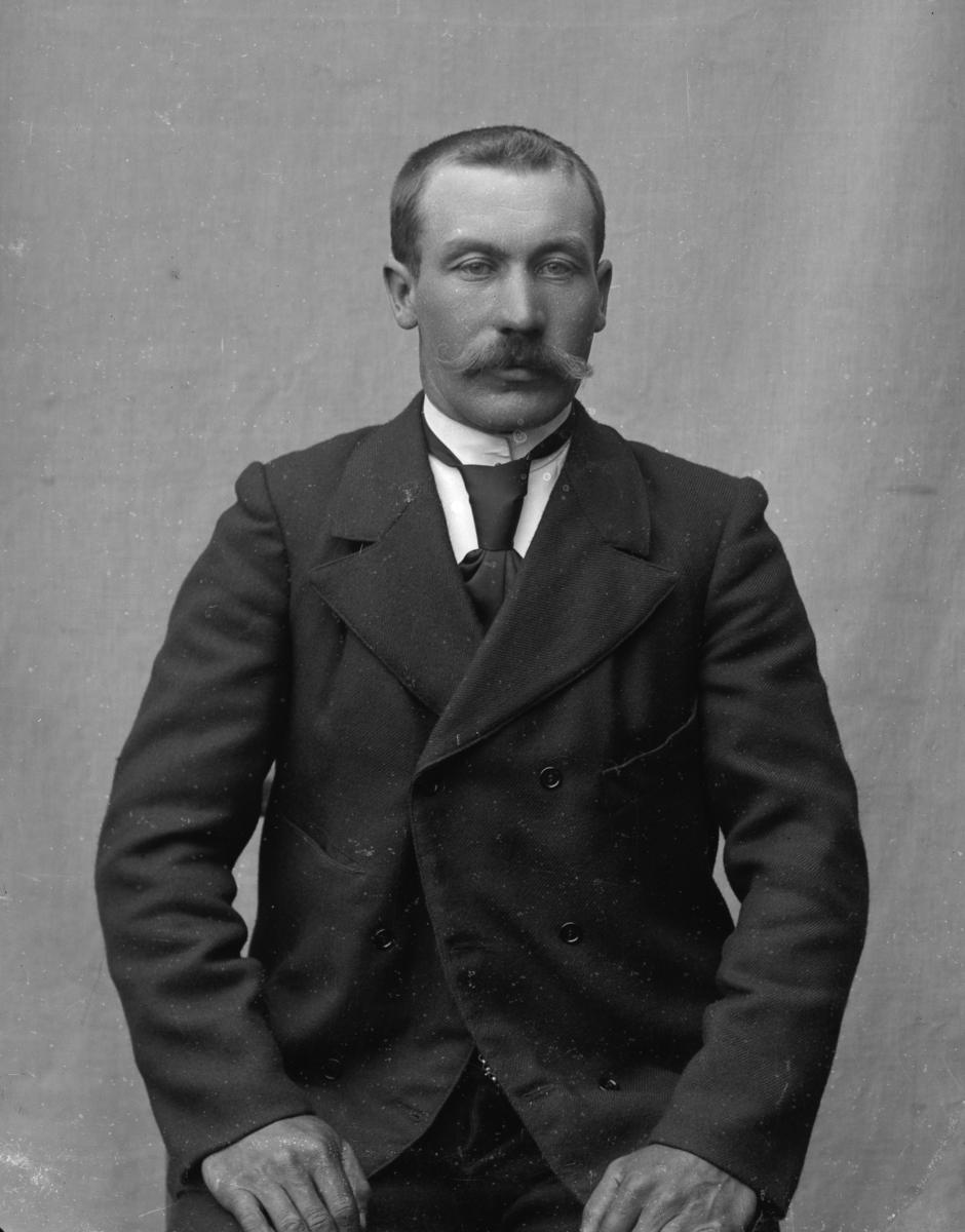 Dresskledd mann sittende foran lerret