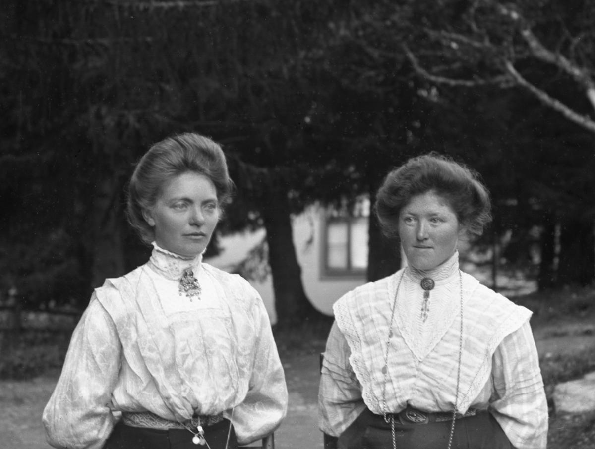 To kvinner kledd i hvite bluser, avbildet på vei, med hus og trær i bakgrunnen