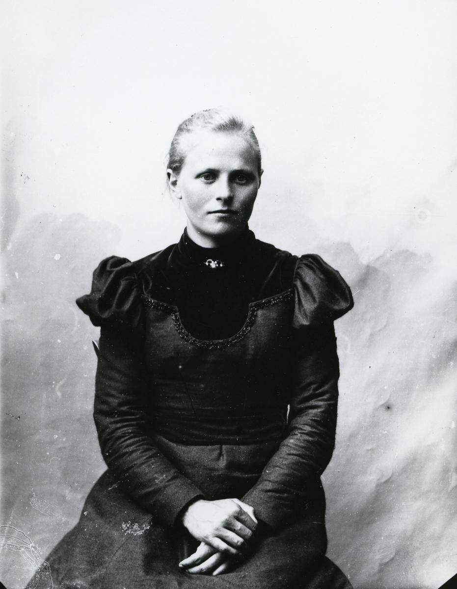 Kvinne i halvfigur, kledd i mørk kjole, lerretbakgrunn