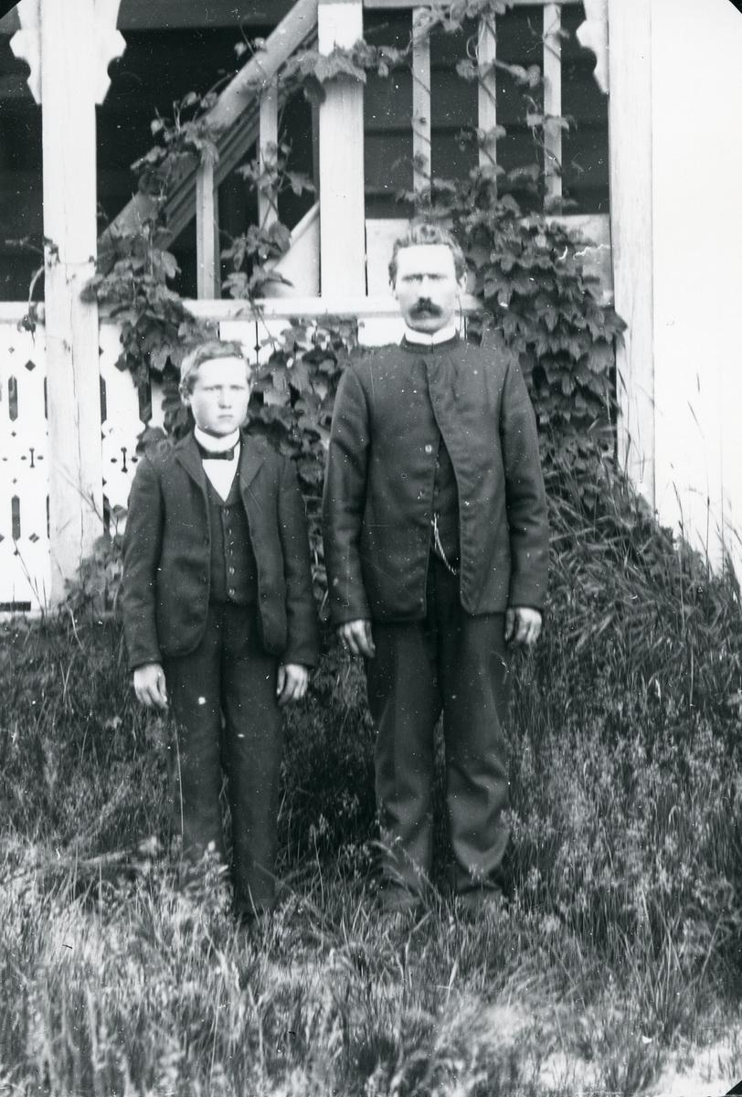 Mann og ung gutt i hage, foran svalgang med sveitserstilsornamentikk