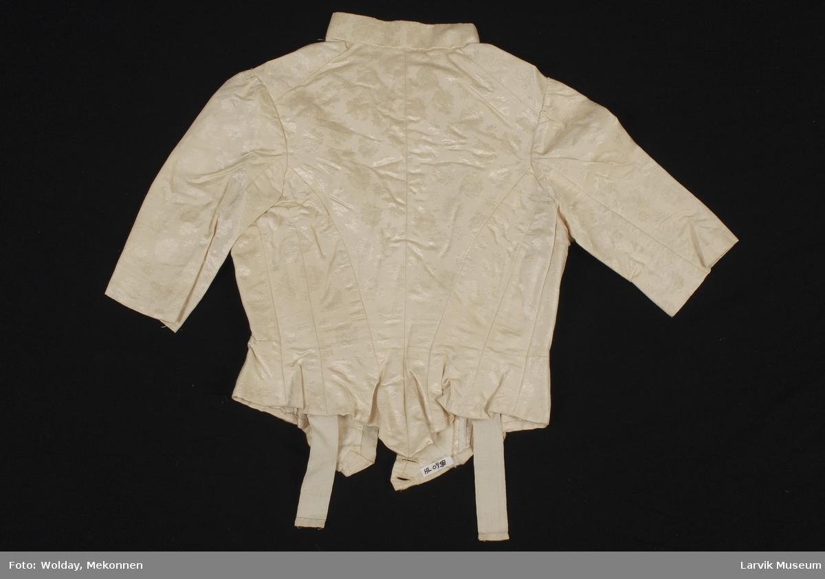 Form: Innsvingt jakke med spiler. kinakrage. Stofftrekte knapper i front, 3/4 lange ermer,  Jakken former en spiss foran og bak. innerbelte med hemper. Mønstervevd stoff med blomster.Silkedamask.