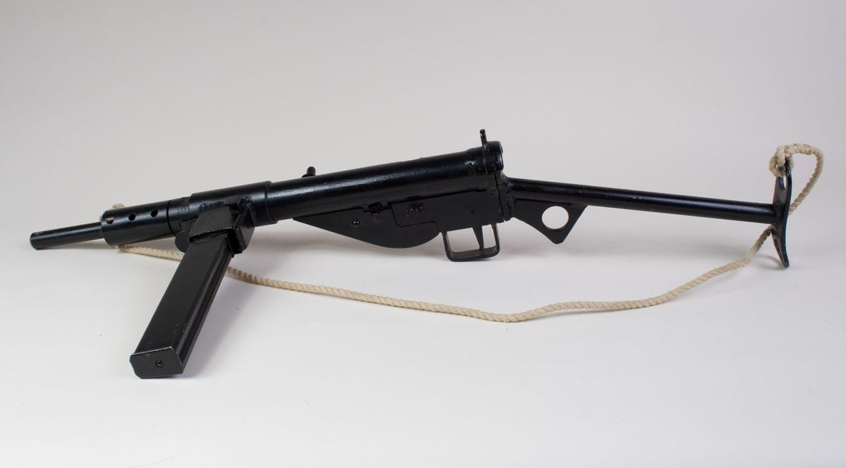 Maskinpistol av typen Stengun Mark II, kaliber 9 x 19 mm Luger.  Laget i stål og med utskiftbart løp. Har magasin med patroner og en tvinnet snor.