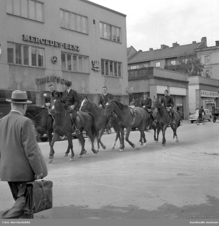 Året var 1958 och den ridande polisen kunde alltjämt dyka upp på stadens gator. Här passerade man Philipssons Bil i korsningen Norra Järnvägsgatan-Nybrogatan. Polisrytteriet i Sundsvall startade i början av 1933 och som mest fanns det tio hästar i stallet. Verksamheten pågick fram till december 1964 då de åtta kvarvarande hästarna skickades söderut. Då skiljdes också konstapeln längst fram till höger, Ingemar Rindestad, från sin tjänstehäst Shah. Ekipaget hade samma år erövrat SM-guld i fälttävlan.