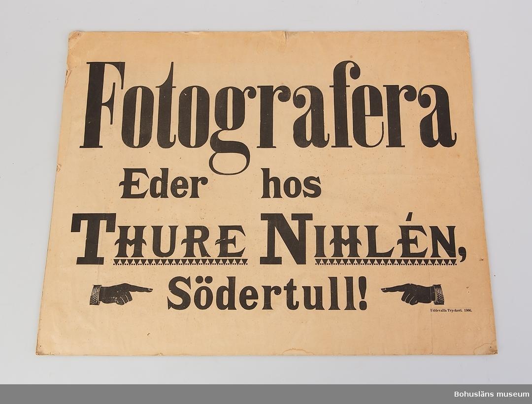 """Rektangulär pappskylt med svart text mot ljus botten:  """"Fotografera  Eder hos  Thure Nihlén,  Södertull"""" I höger hörn: """"Uddevalla tryckeri 1906"""".  För uppgifter om fotograf Thure Nihlén, ateljén i Uddevalla på Södra Drottninggatan 13 och förvärvet, se UM68.25.001."""