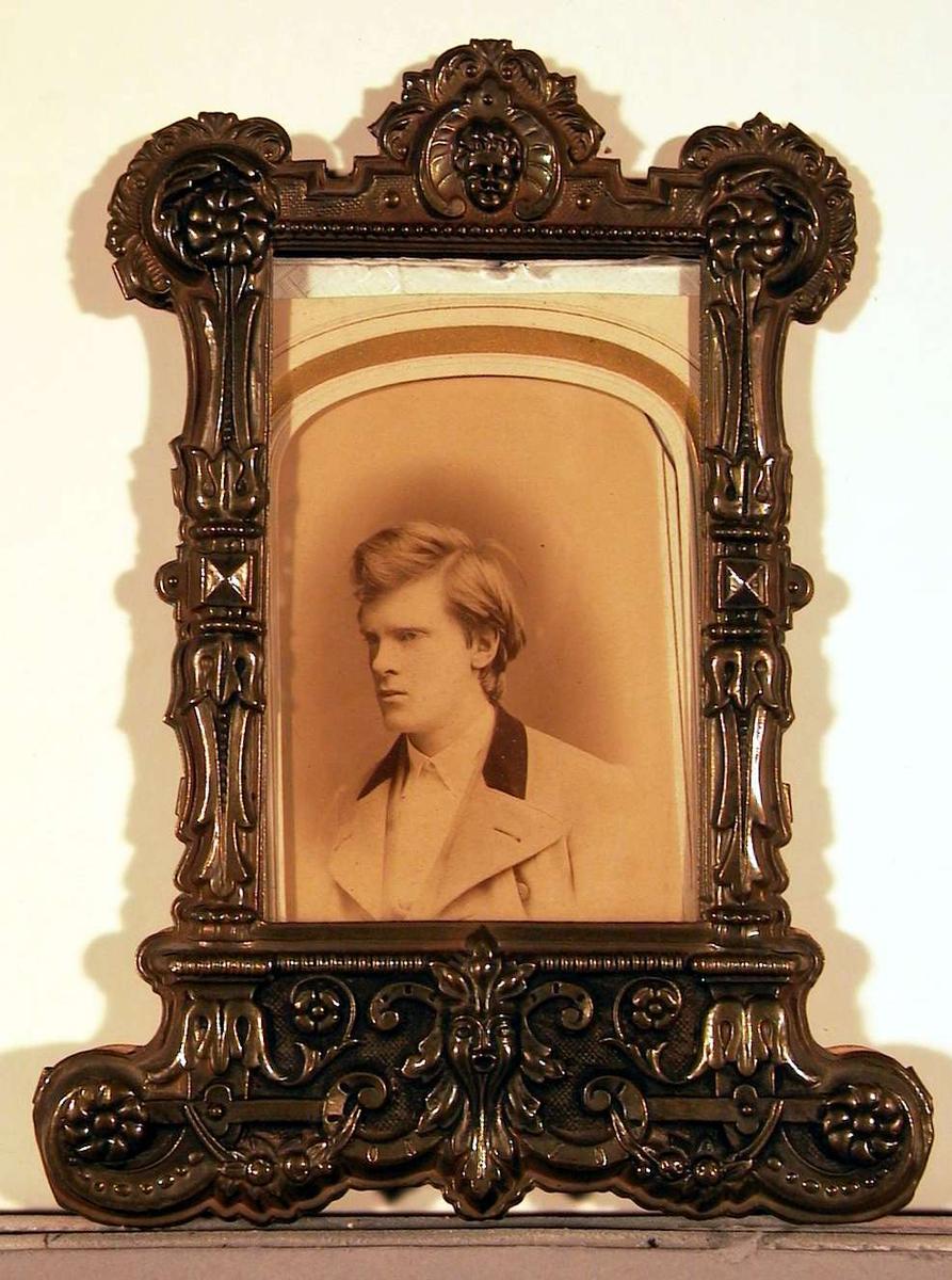 Portrettfotografi av ung mann i lys dress med vest og mørkt bakstykke på reversen.