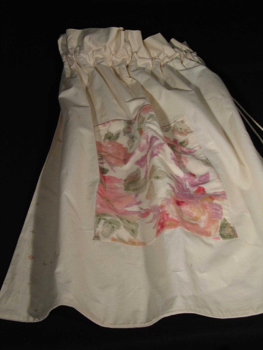 Hvit pose i lerret med løpegang og snor øverst. Den er dekorert på midten med et felt blomstret kretong. (27 x 32 cm)