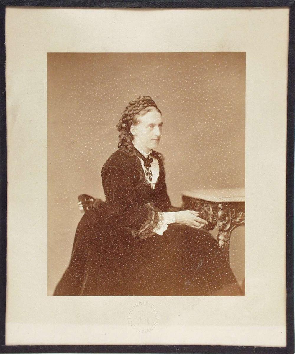 Kvinne sittende ved et bord iført en lang mørk kjole.
