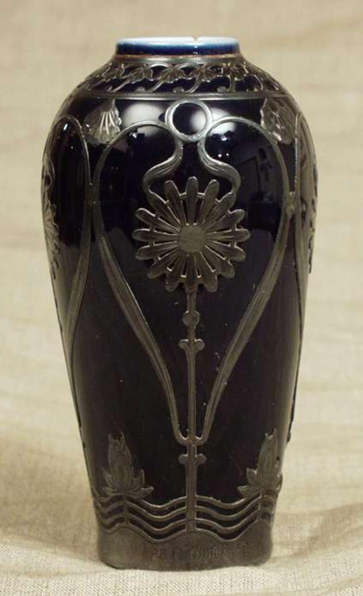 Vasen har blomsterdekor i metall.
