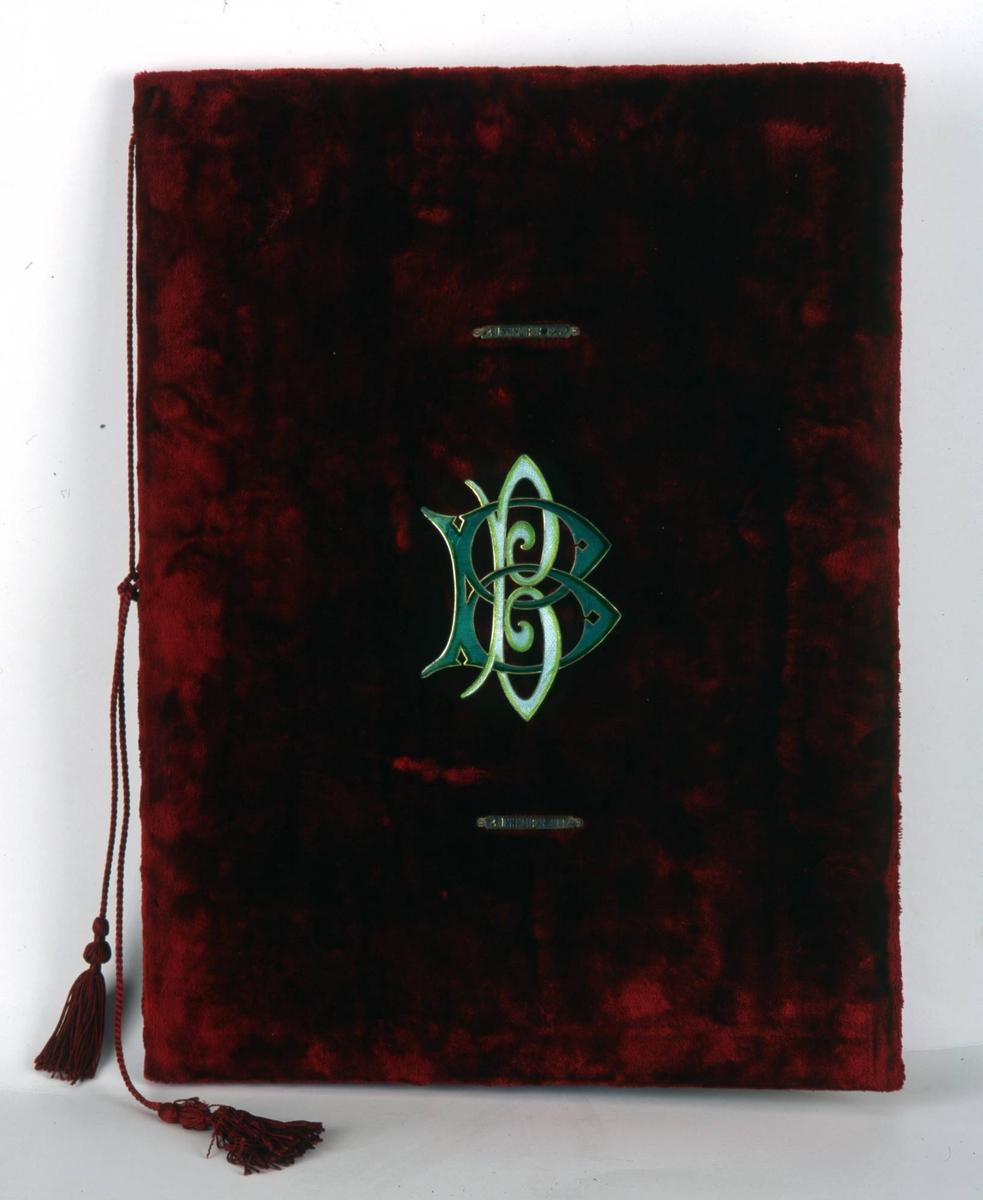 Adresse innbundet i rød fløyel med BB's monogram i grønn emalje. Den har er foret med hvit silke. Adressen har laurbærblad på hver side og BB's initialer i gull.