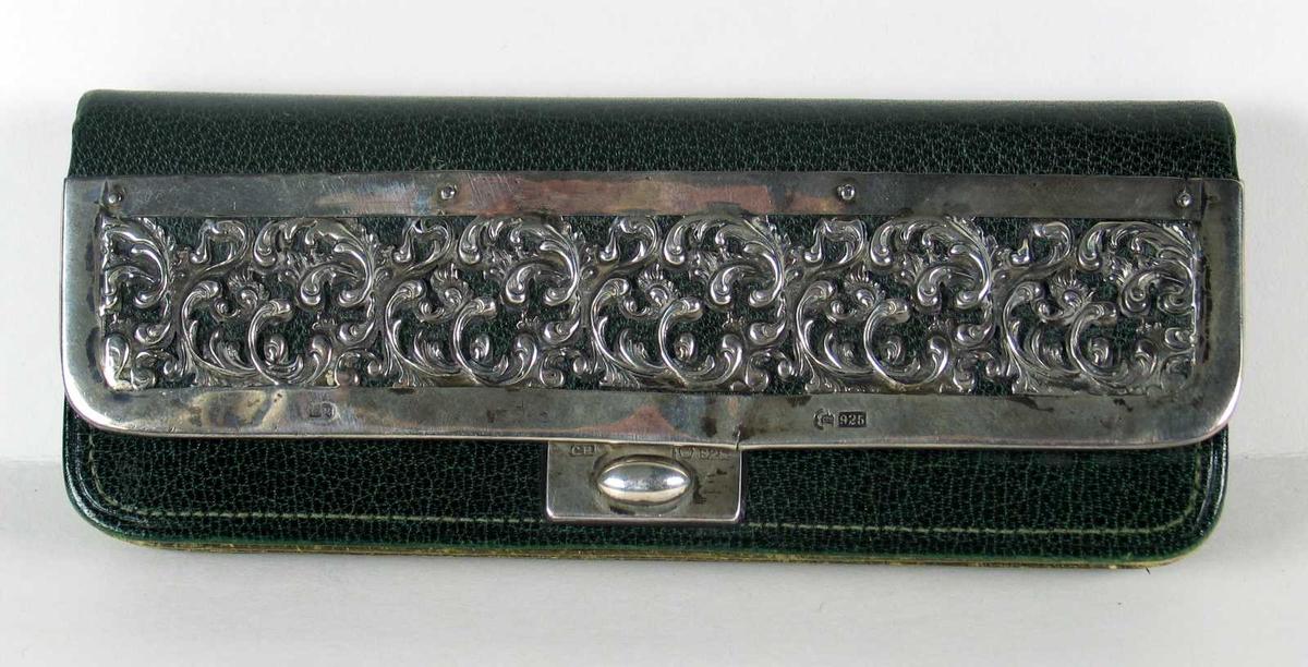 Portemoné i grønt skinn innvendig fôret med ufarget lær. På klaffen er det påsatt sølvbeslag med gjennombrutt akantusbord. Lomme på baksiden i tillegg til seks lommer innvendig.