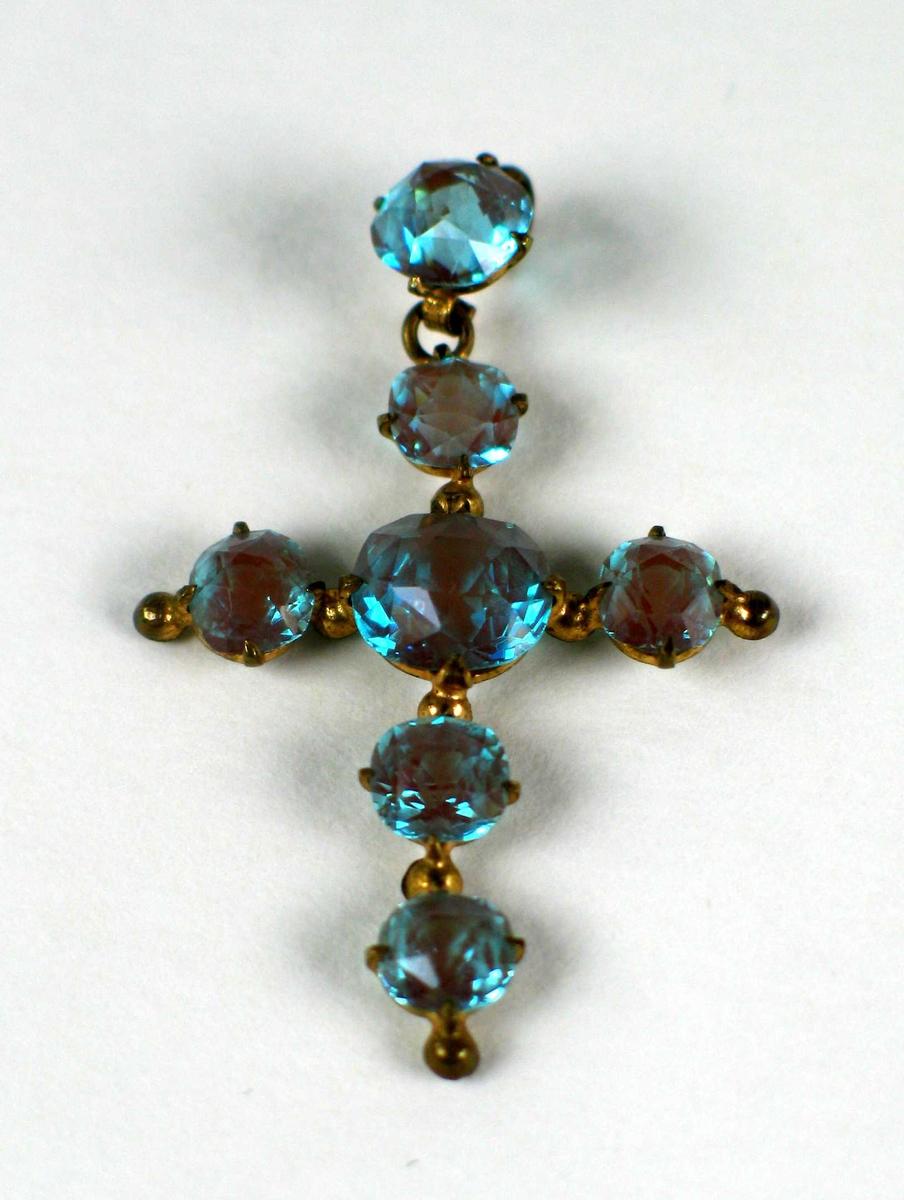 Korsformet anheng antatt i gull med syv slipte turkise steiner. Smykket ligger i et svart etui.