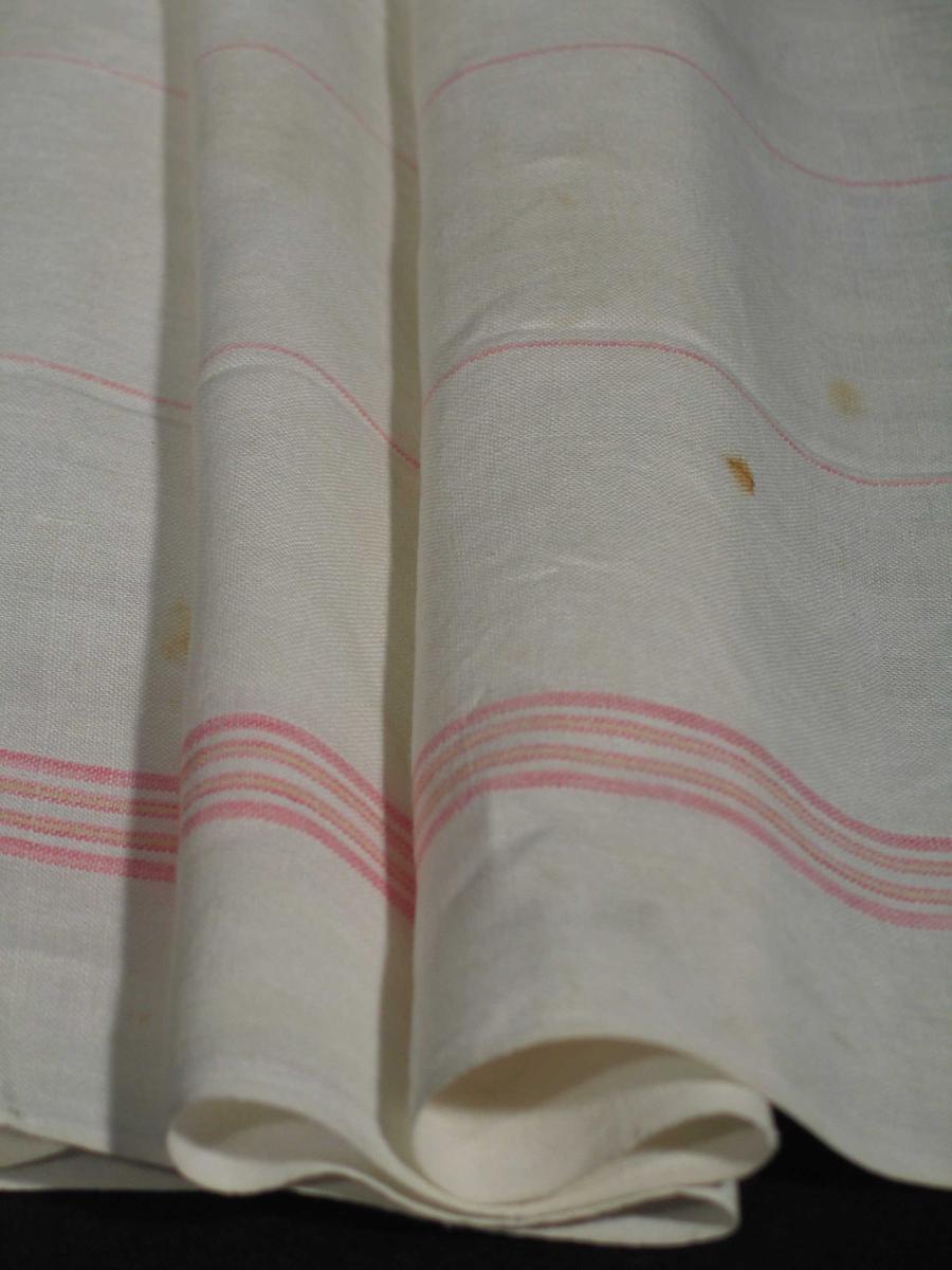 Hvitt glasshåndkle i lin med røde og gule striper i bord øverst og nederst. Fem smale røde striper fordelt over flaten. Stripene ligger i renningen, og er antatt av bomull. Vevbredden 66 cm med jare, maskinsydde falder øverst og nederst..