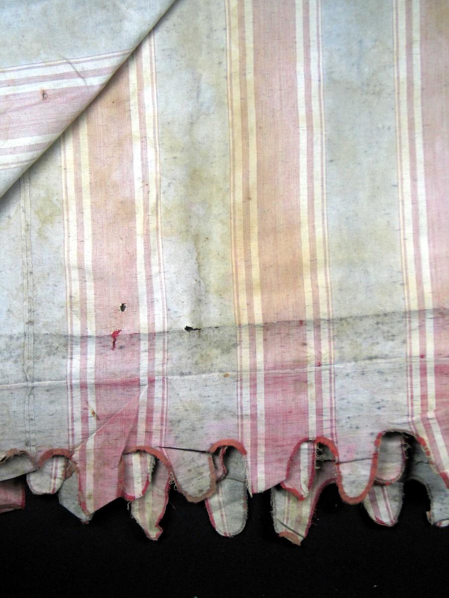 Markise i kanvas med tungekant i front. Stoffet er stripet i burgunder og grått. Merker etter spikerfeste.