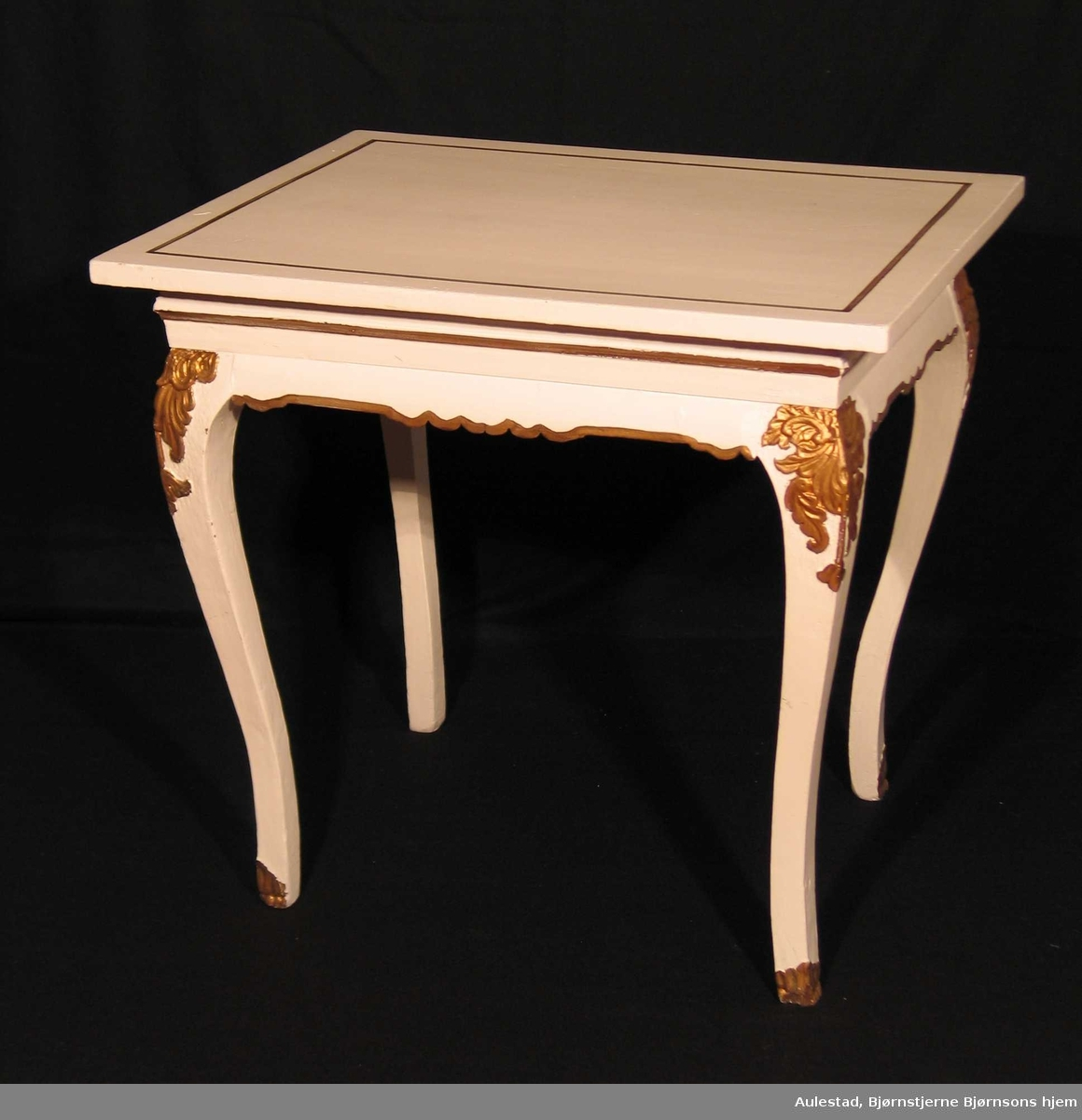 Hvitmalt bord med detaljer malt i bronse. Benene er laget i gran og bordplaten i bjørk. Benene er svungne og har utskåret skjellmønster øverst.
