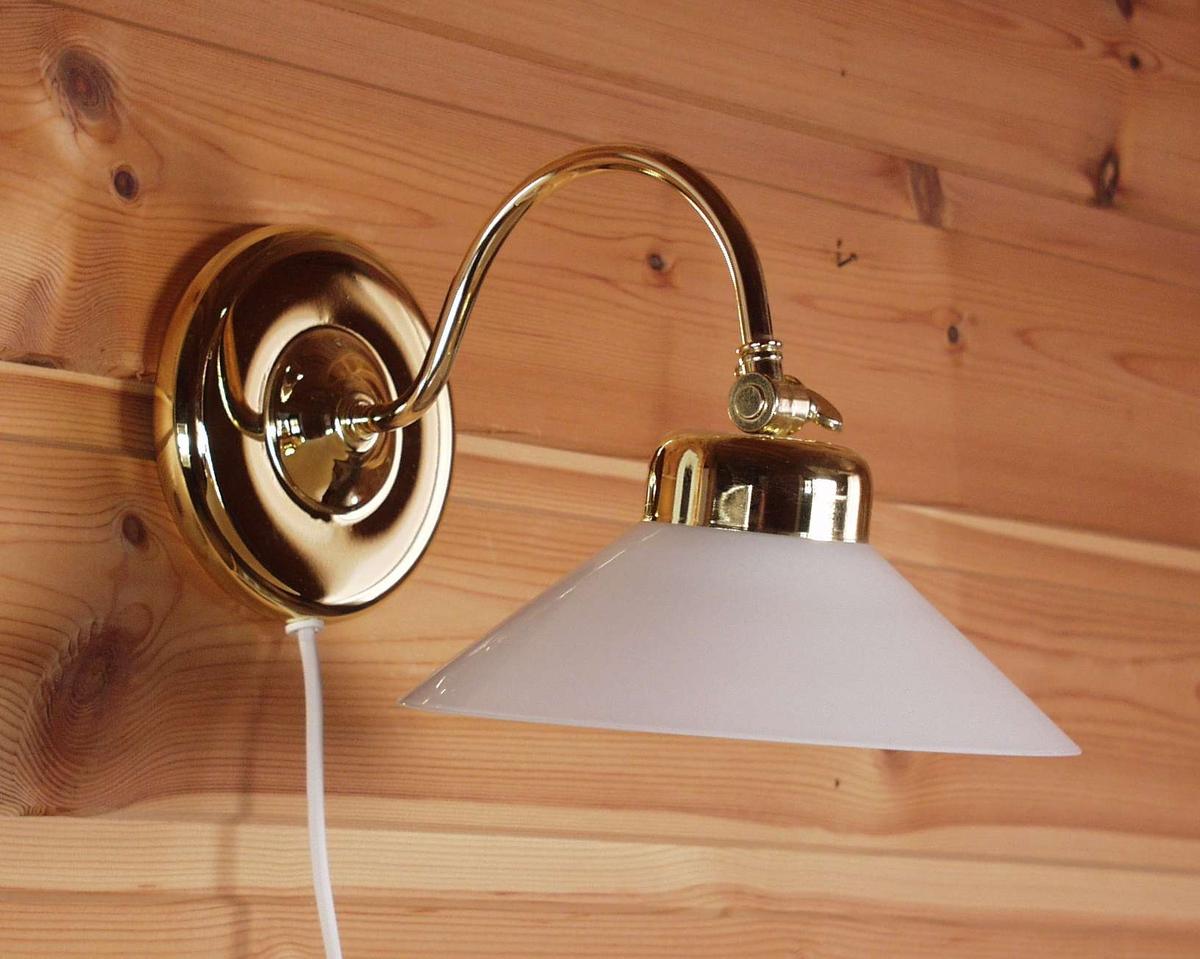 Skomakerlampe i metall med buet arm og rundt veggfeste. Skjermen er i hvitt glass og har skrujustering på toppen.