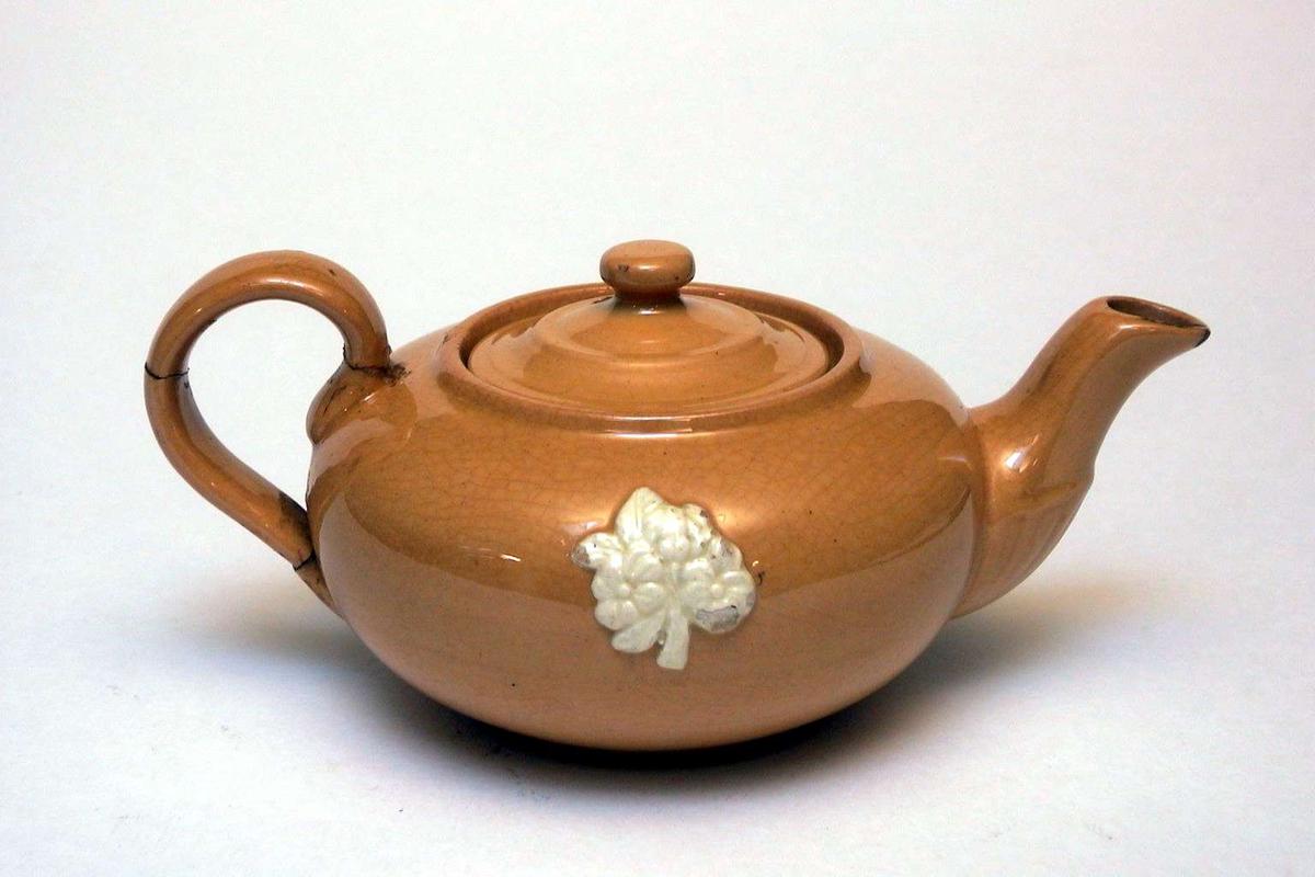 Tekanne m/ lokk av gul keramikk med påsatt blomsterdekor. Dekoren er elfenbenshvit. Hanken er limt. Kannen har ingen produksjonsmerker.
