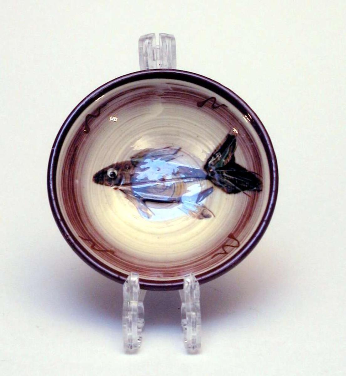 Liten skål i keramikk med fiskemotiv. Skålen har hull for oppheng.