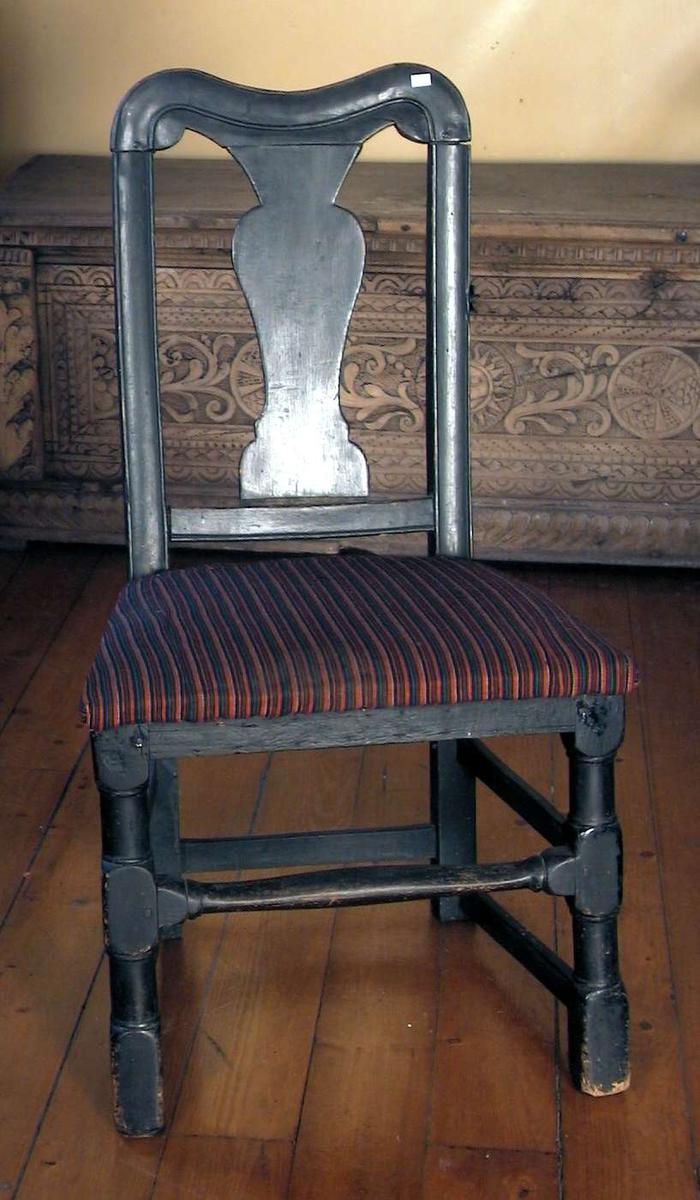 Sortmalt stol med sete trukket med randet bunadstoff.