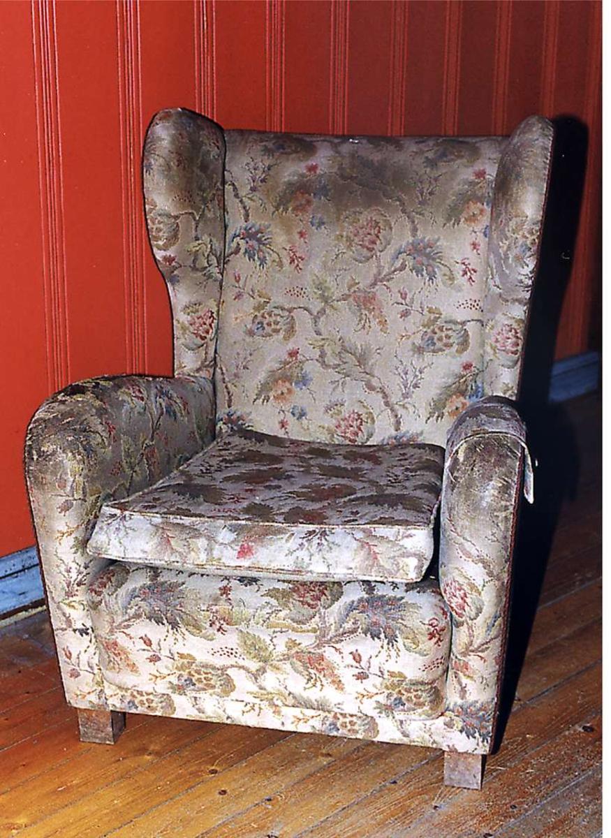 Ørelappstol trukket med blomstret stoff i beige bunnfarge.Trekket er slitt og falmet.