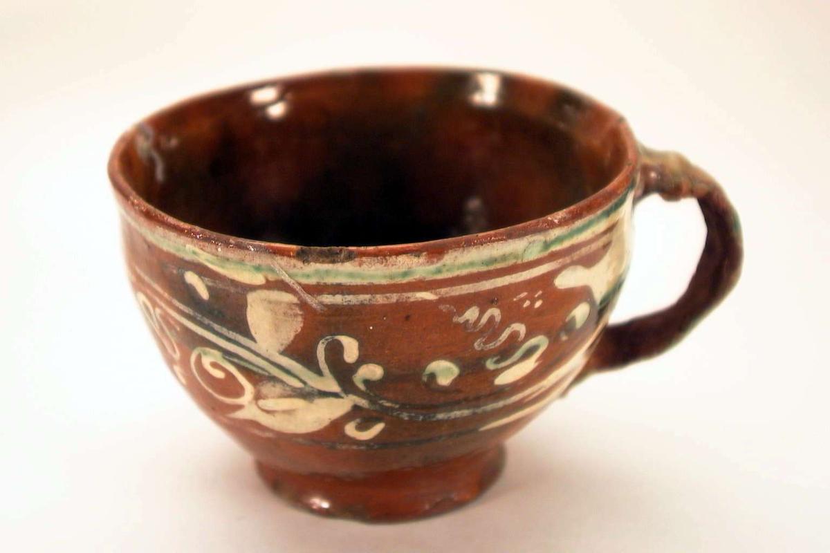 Grovt laget kopp i brunt leirgods med 'meksikansk' dekor. Koppen er påsatt ny hank.
