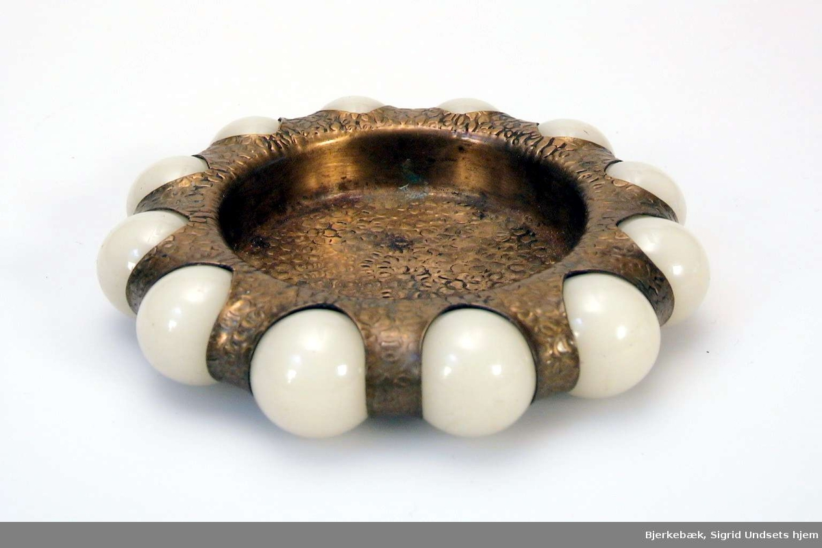Smykkeskål i messing, med kuler laget av ben som dekor langs kanten.