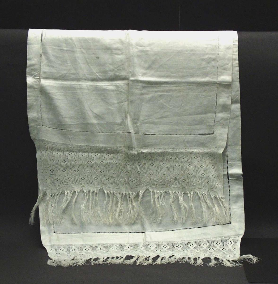 Løper av hvit lin. 4 cm. bred fall på sidene, sydd med hullfall, vekkslitt tråd for tvinning av 'stolpene'. 13 cm  bredt sprang (+ 9 cm frynser) i hvit tvunnet lin i hver kortende.