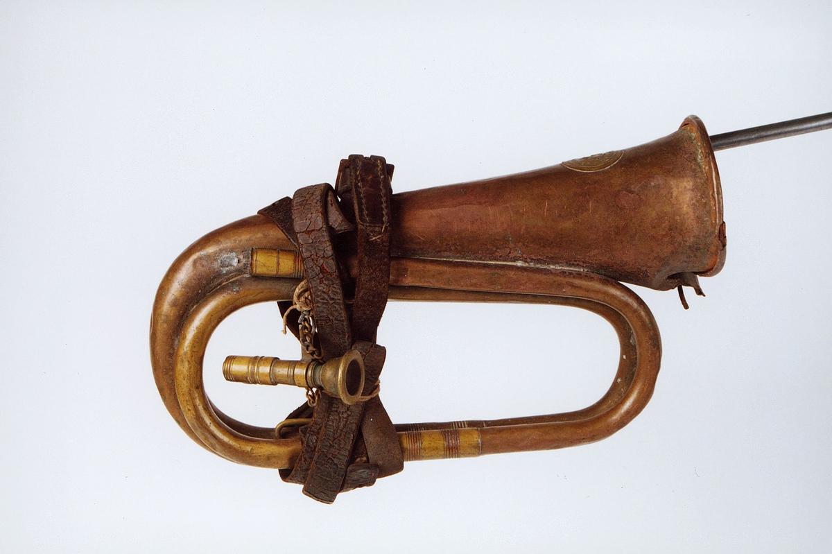 Postmuseet, gjenstander, posthorn, trompettype, munnstykke henger i en lenke, lærrem surret rundt hornet, tuten er skadet.