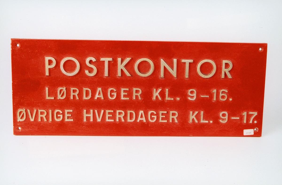 Tekst: Postkontor Lørdager kl. 9 - 16. Øvrige hverdager kl. 9 - 17. Sølvskrift på rød bunn.