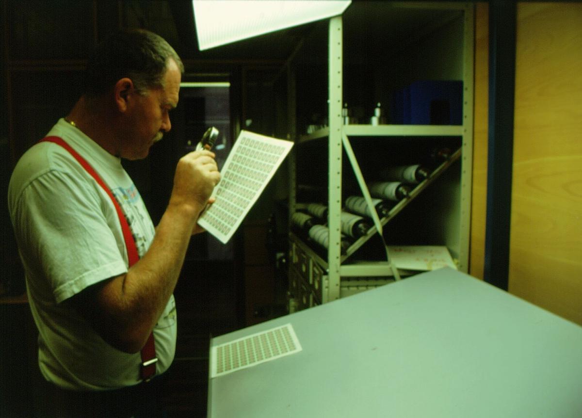 frimerketrykking, Norges bank Seddeltrykkeriet, rotasjonspresse, Goebel frimerkerotasjon, frimerker i produksjon, lysbord, trykker Åsmund Vold Hansen kontrollerer og sammenligner fargene på frimerkearkene med lupe