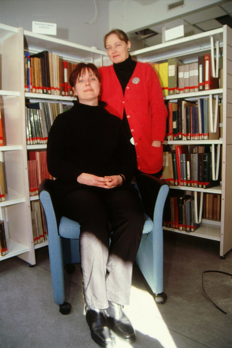 postmuseet, Kirkegata 20, biblioteket, Elin Eskerud sitter og Torgunn Haugaard står foran bokhyllene, stol