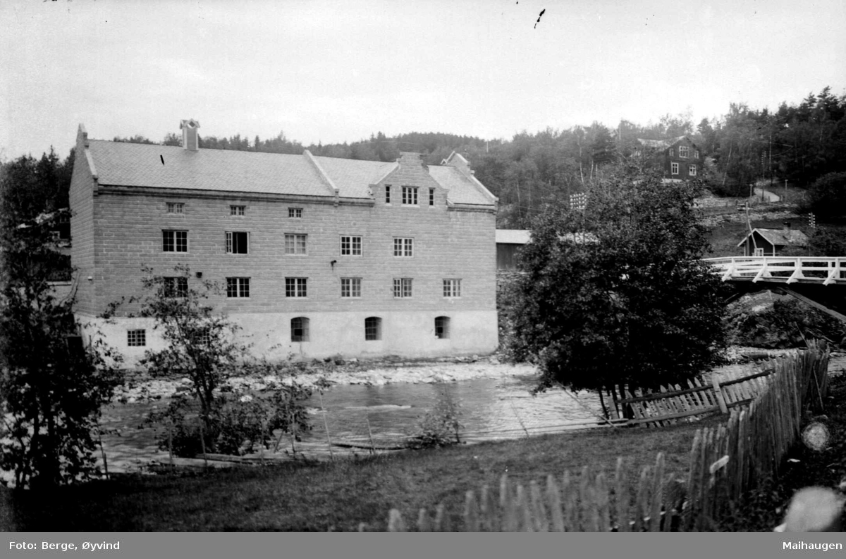 En bygning, trolig fabrikk, i forgrunnen elv
