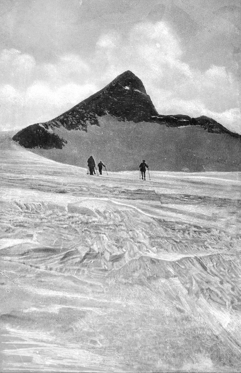 Tre skiløpere, foran høy fjelltopp, vinter