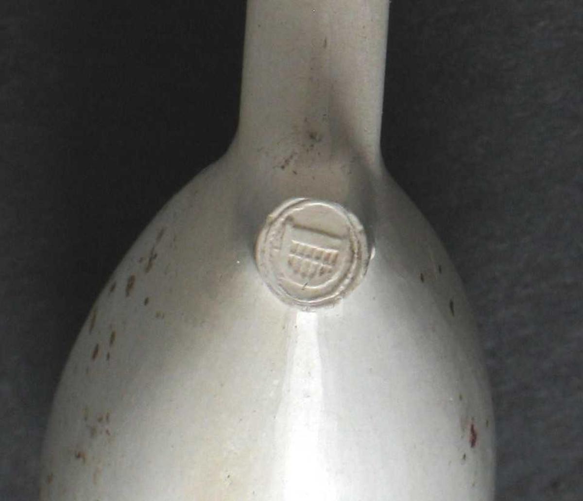 Krittpipe, Hollandsk form, stempel under  knasten med opprutet D (kurv?).    Pipe av vanlig Goudaform, neststørste type,  smal knast med en liten prikk på den  ene siden. ornamer felt midt på stilken.  Litt flekket på den ene side av hodet.