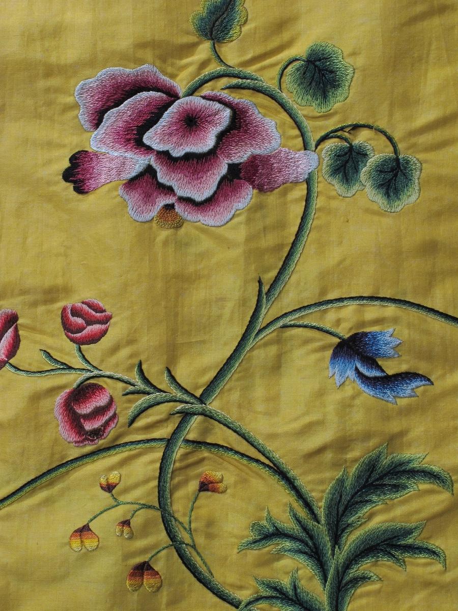 Del av en kjole,  ca. 1750   Silke,  sterkt gult. Brodert blomsterbord.   H. 88,5. Total L. 361. Opprinnelig et skjørt med bredt polykromt blomster  broderi langs nedre kant, slyngende gren. Under denn  en hvit bølgebord med smått rutemønster.  I senere tid, antag. 1900 tallet er skjørtet fjernet  fra linningen. det er påsydd en brunt bånd med ma  skin. Langs øvre kant på en av de fem breddene er  påtegnet med blyant et lignende blomstermotiv som  bede, men mer smått og tett. En opprinnelig lerrets  lomme henger på.  Tilstand a meget god.