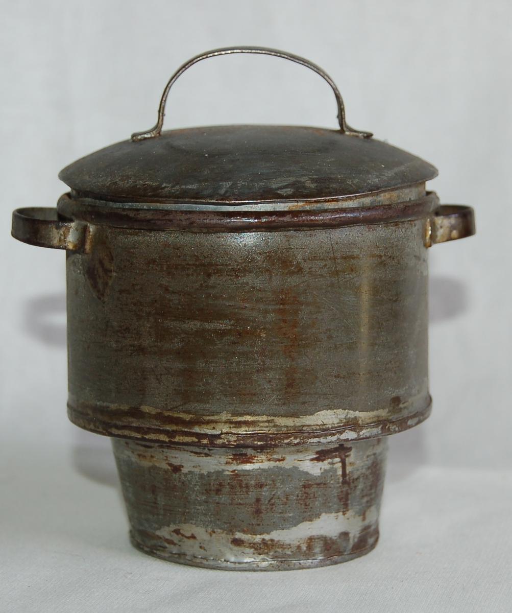 Sirkelformet tverrsnitt, smalere del som passer ned i komfyren under.