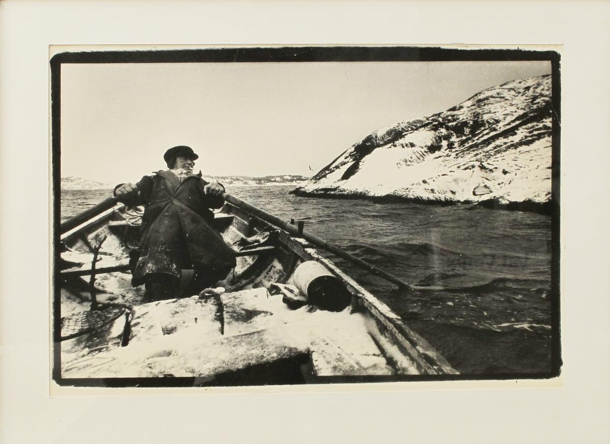 Roende fisker, th. snøkledd fjell.  Fisker, pram, årer, roing, snø,