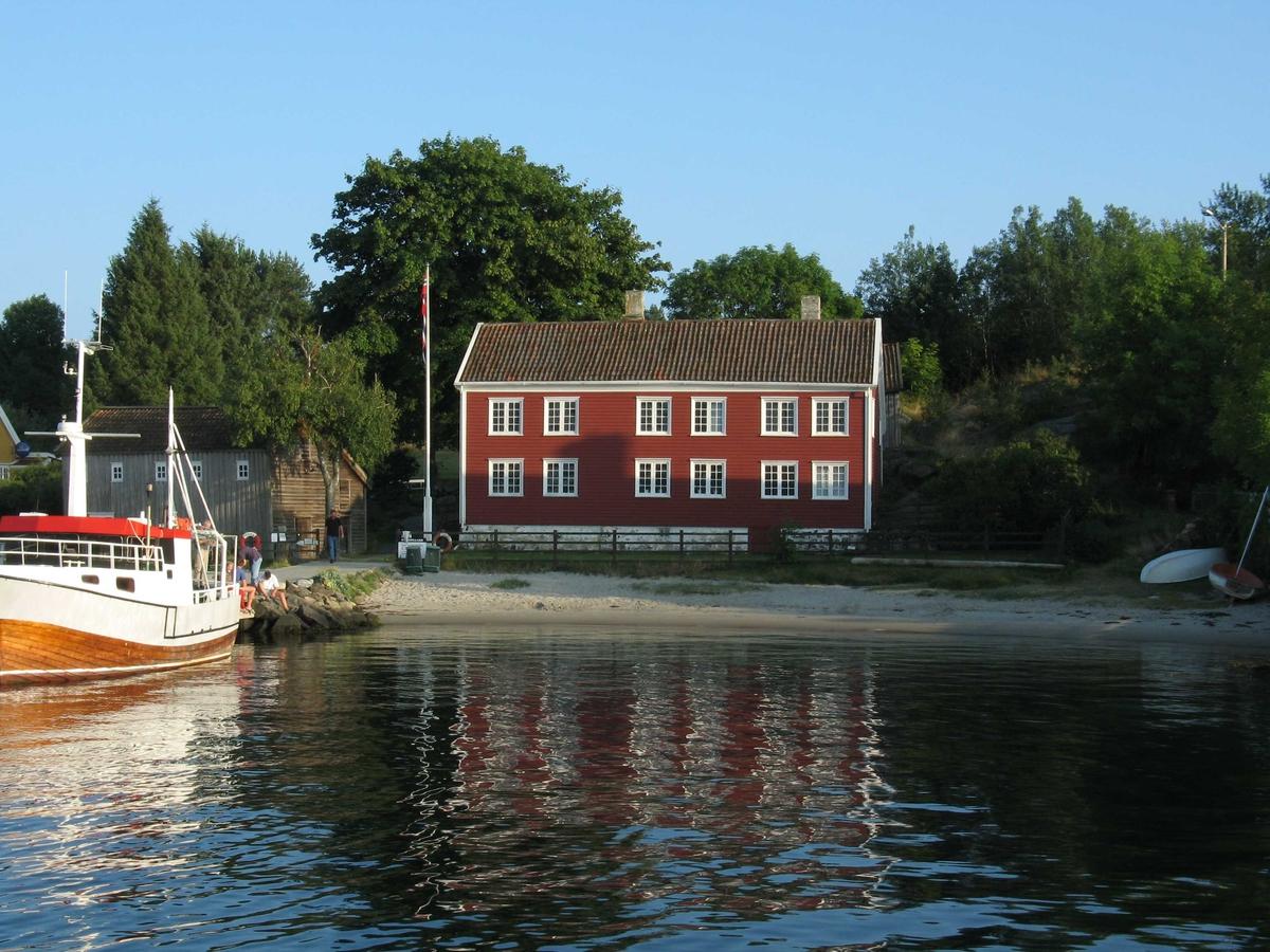 Merdøgaard. Fasade mot sjøe, sett fra båt. Kveldsbelysning.