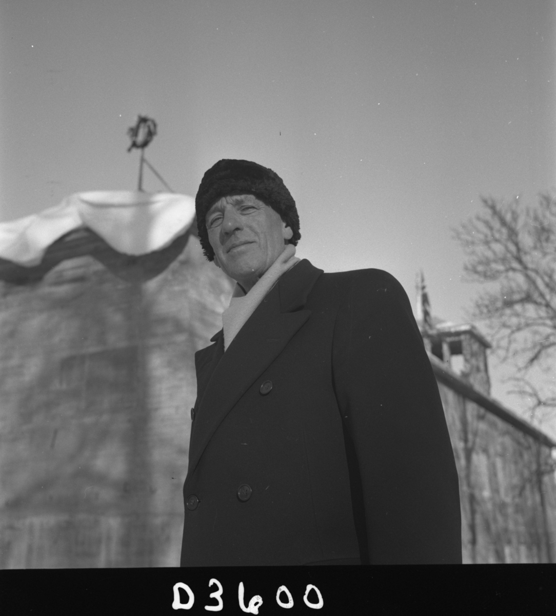 Museumsbygningen  på Langsæ.  Kranselag, kransen henger i en stang på taket i bakgrunnen. Vinter med snø. I forgrunnen fylkeskonservator og museumsbestyrer Albert Ugland.