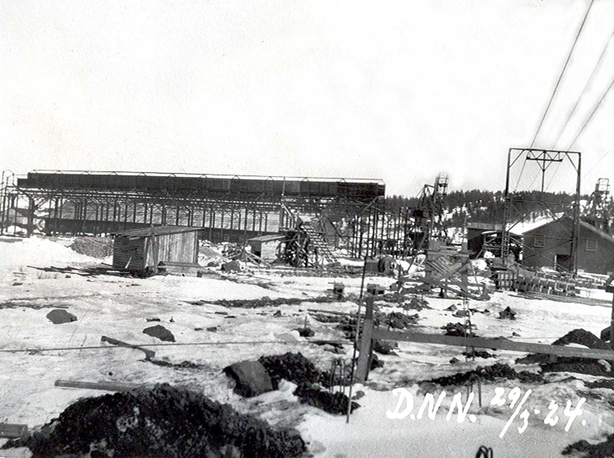"""""""29/03-1924"""" Nitriden. Bygging av stekeribygning for steking av elektrodekull. Jernkonstruksjoner. Kraner på kai i bakgrunnen. Lagerbygning for bauxitt og taubanemast. Tromøy i bakgrunnen."""