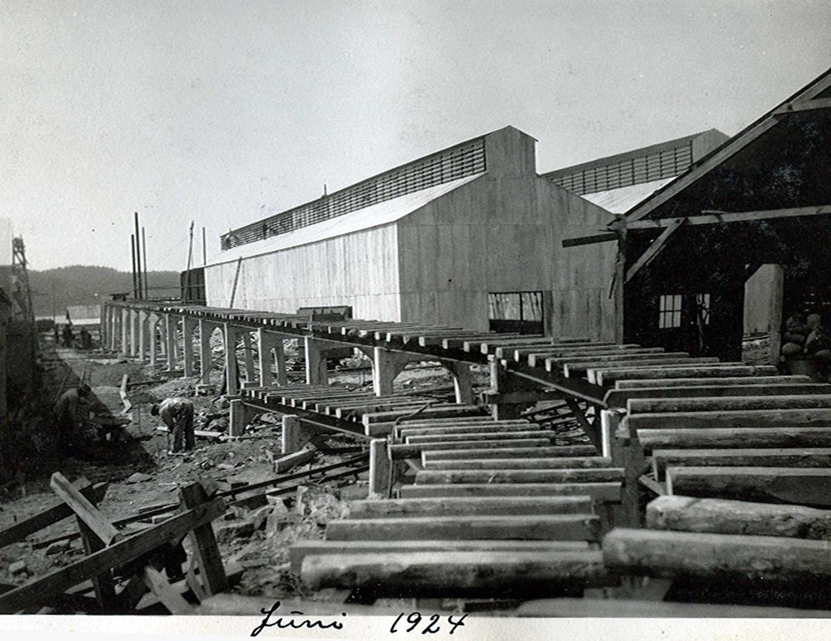"""""""xx/06-1924"""" Nitriden. Skinnegang, """"høybanen"""", med bærende konstruksjoner og sviller. Skinnegangen er for intern transport med traller trukket av dieseldrevet lokomotiv. I bakgrunnen til høyre bygninger for steking av elektrodekull. Kaianlegg til venstre."""