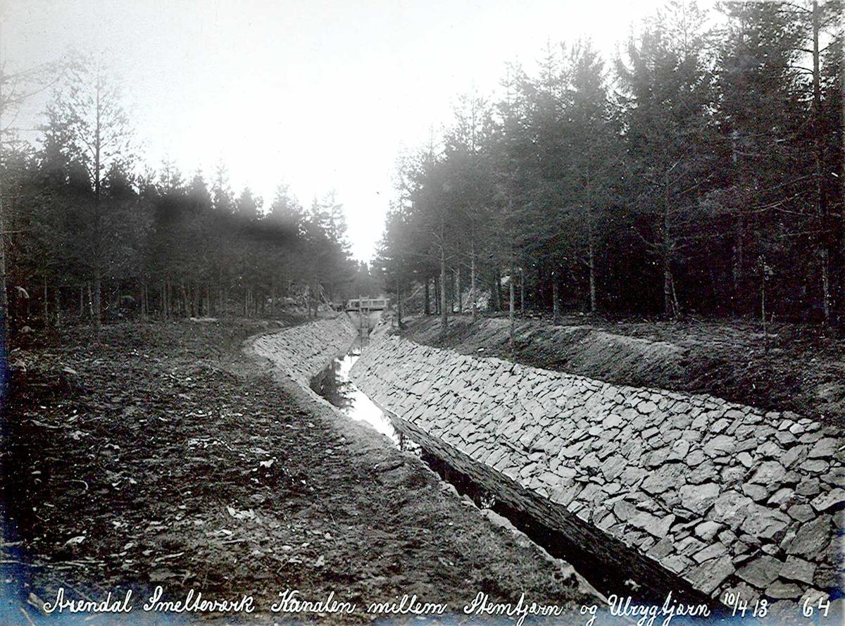 """""""10/04-1913"""" Nitriden. Smelteverket. Steinsatt kanal mellom Stemtjern og Ulfsryggtjern, vannkildene til bedriftene. I enden av kanalen, dam ved Ulfsryggtjern. Stemtjern ligger lavere. Damkrone med gangbru."""
