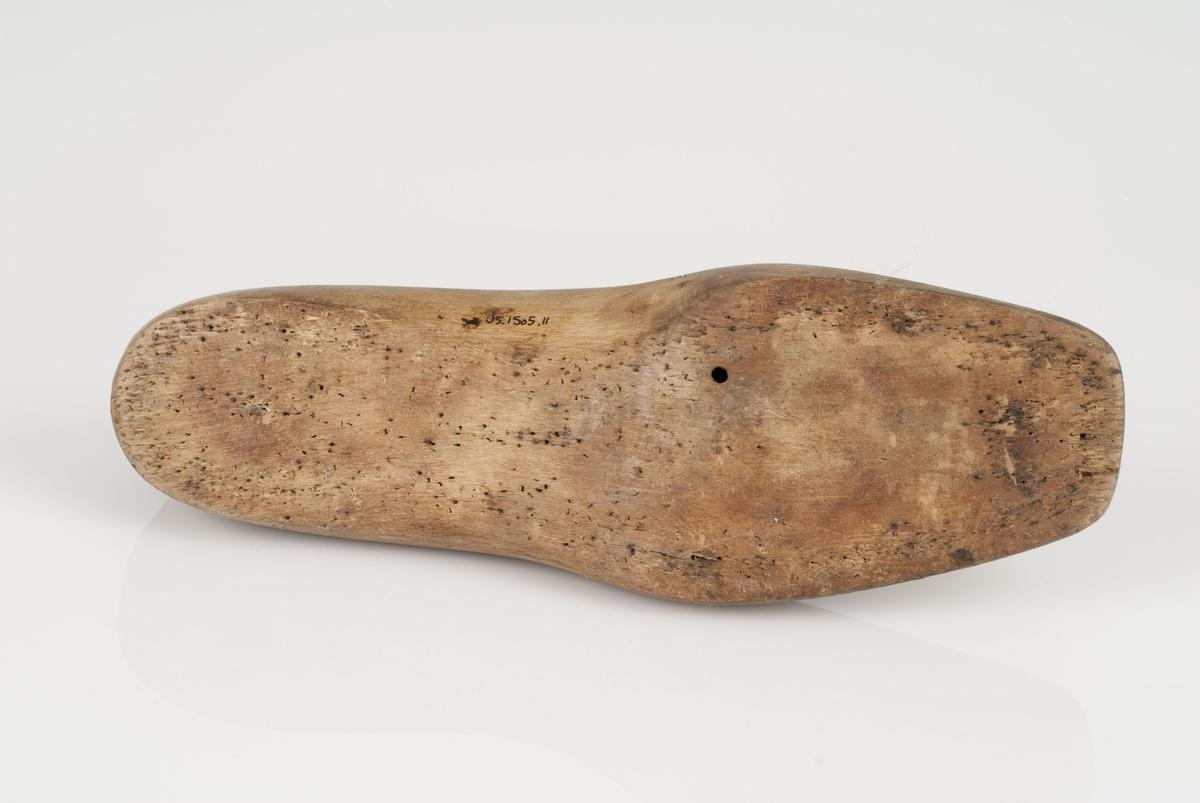 En tremodell i to deler; lest (A) og opplest/overlest (kile) (B). Høyrefot i skostørrelse 42, og 8 cm i vidde.