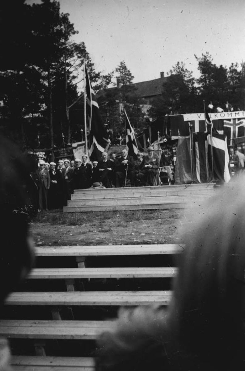 Forsamling ute på en scene med flaggsmykket talerstol. Her sees bl.a. Johan Nygaardsvold.