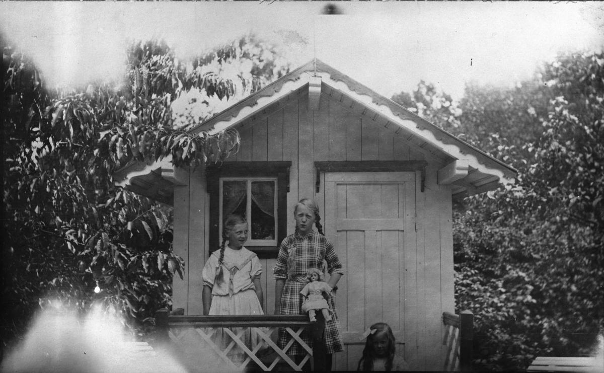 Tre småpiker, dukke, dukkehus, busker
