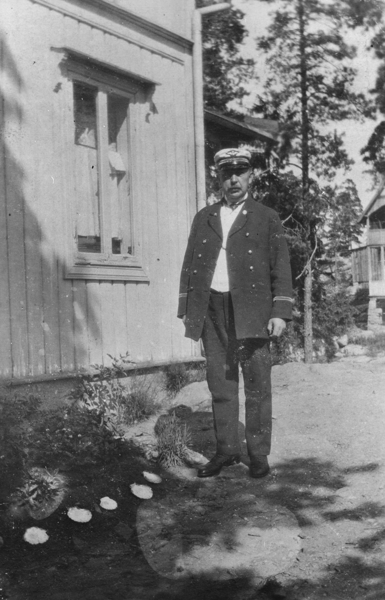 Eldre mann i jernbaneuniform, ved siden av hus.